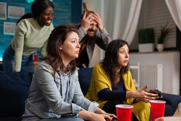 Amis multiethniques tristes après avoir perdu la compétition de jeux vidéo tout en socialisant à l'aide d'une manette sans fil assis sur un canapé, buvant de la bière tard dans la nuit sur une grande télévision.