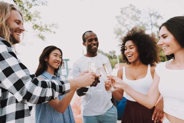 Amis multiraciales boivent du champagne sur la plage