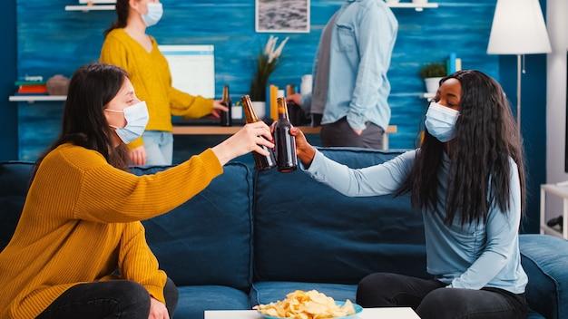 Amis multiraciaux avec des masques dégustant une bière à une nouvelle fête normale dans le salon en respectant la distance sociale pour empêcher la propagation du virus