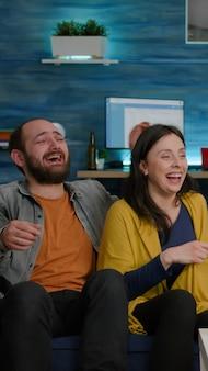 Amis multiraciaux riant ensemble assis sur un canapé