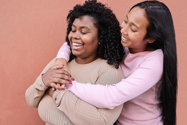 Amis multiraciaux s'amusant ensemble en plein air dans la ville - accent principal sur le visage de la fille droite