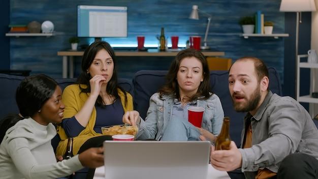 Amis multiraciaux se détendre sur un canapé en regardant un film comique
