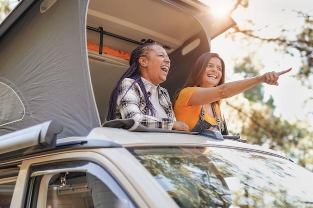 Des amis multiraciaux seniors profitent de vacances dans la nature avec un mini van - femmes mûres en voyage avec camping-car