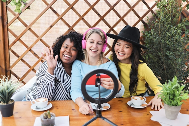 Amis multiraciaux en streaming en ligne avec caméra de téléphone portable à l'extérieur au restaurant