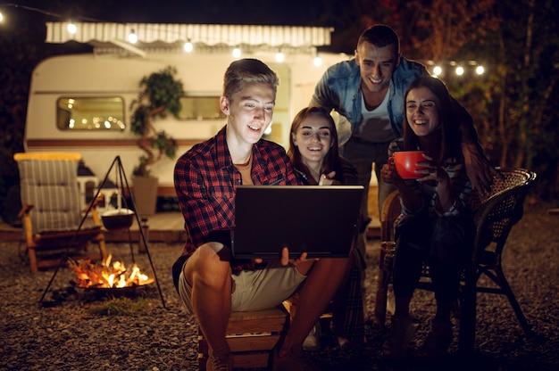 Amis avec ordinateur portable près du feu de camp dans la nuit, pique-nique au camping dans la forêt