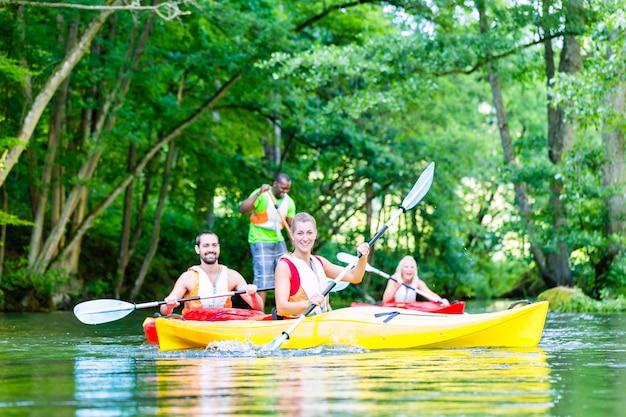 Amis pagayer avec canoë sur la rivière forestière