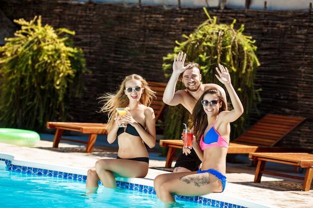 Amis parlant, souriant, buvant des cocktails, saluant, se relaxant près de la piscine