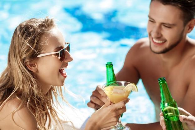 Amis parlant, souriant, buvant des cocktails, se reposant, se relaxant près de la piscine