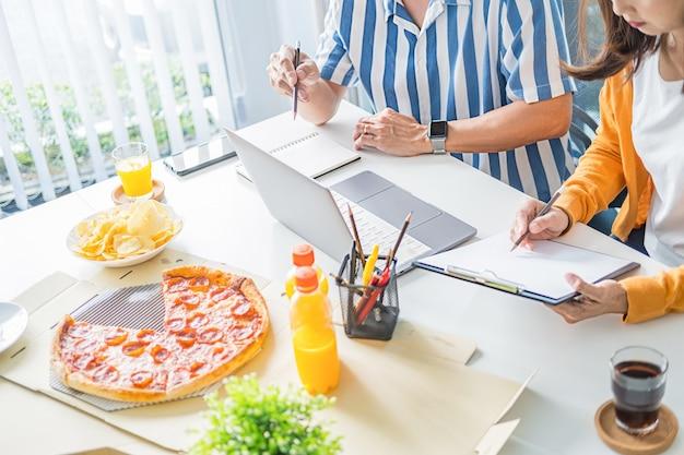 Des amis parlent et mangent des pizzas dans la salle de réunion.