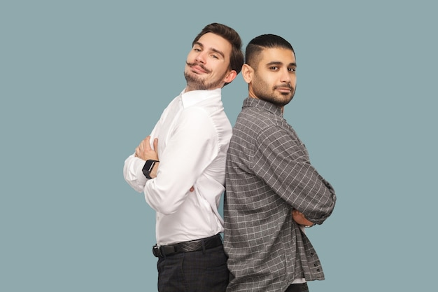 Amis ou partenaires debout avec les bras croisés regardant la caméra avec un visage fier