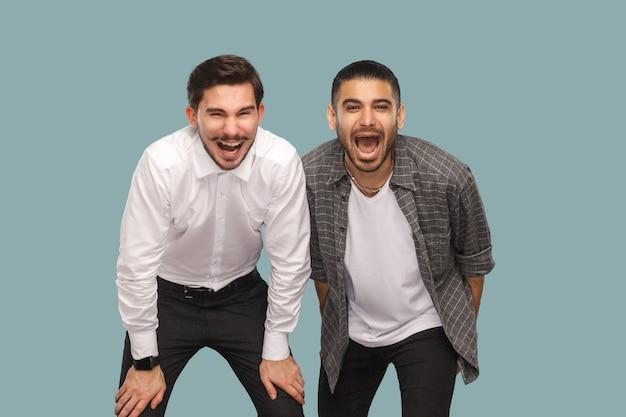 Amis ou partenaires debout et regardant la caméra et riant la bouche ouverte