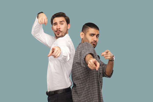 Amis ou partenaires debout regardant et pointant vers la caméra avec des visages étonnés drôles