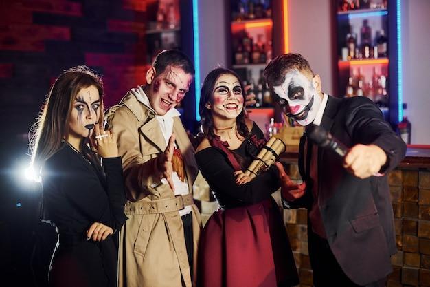 Des amis participent à la soirée thématique d'halloween avec un maquillage effrayant et des costumes s'amusent et posent ensemble pour la caméra.