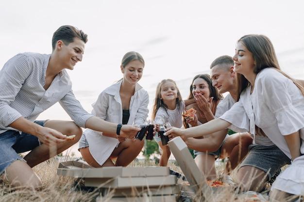 Amis de pique-nique avec pizza et boissons, boire et manger avec joie, journée ensoleillée, coucher de soleil, entreprise, amusement, couples et maman avec bébé