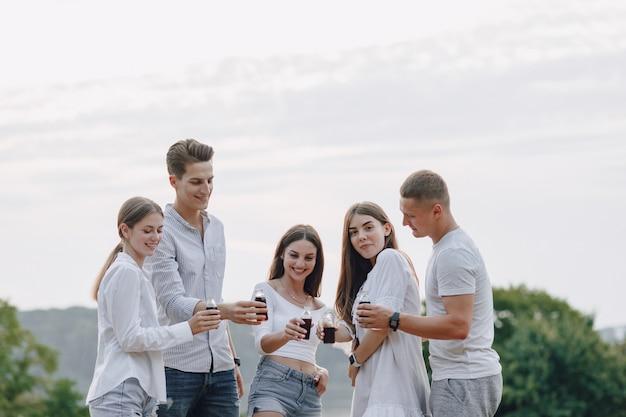 Amis de pique-nique avec pizza et boissons, journée ensoleillée, coucher de soleil, entreprise, amusement, couples et maman avec bébé