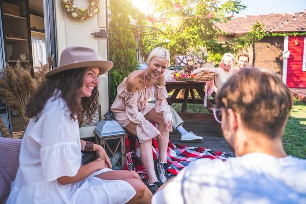 Des amis pique-niquent avec un camping-car dans un pré vert