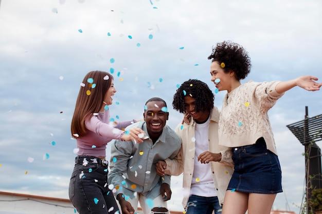 Amis de plan moyen faisant la fête avec des confettis