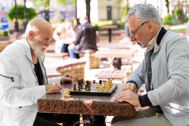 Amis de plan moyen jouant aux échecs