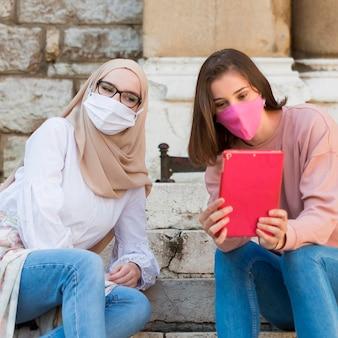 Amis de plan moyen prenant selfie à l'extérieur