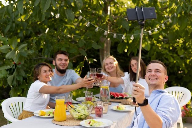 Amis de plan moyen prenant un selfie à l'extérieur