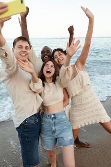 Amis de plan moyen prenant le selfie sur la plage