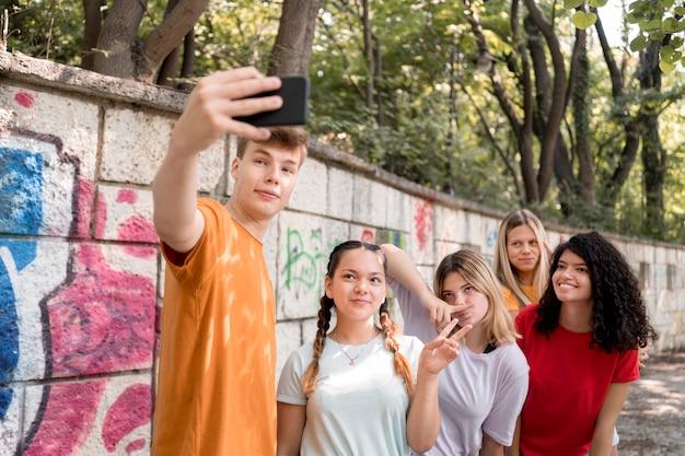 Amis de plan moyen prenant des selfies ensemble