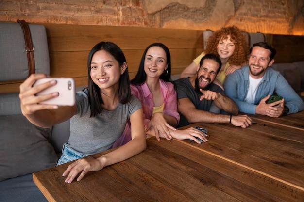 Amis de plan moyen prenant des selfies