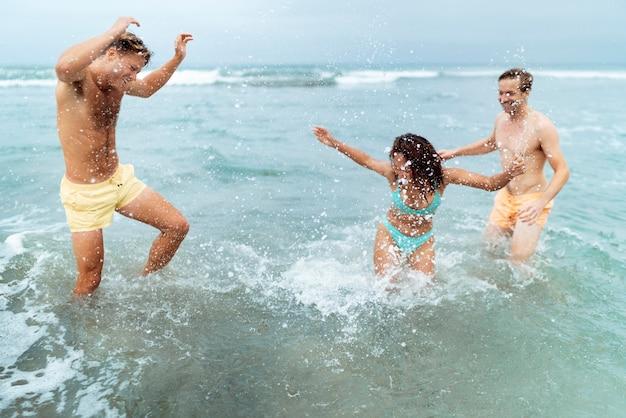 Amis de plan moyen s'amusant dans l'eau