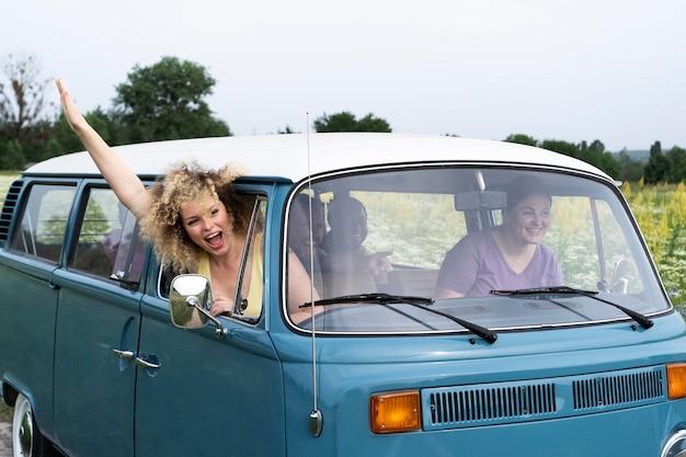 Amis de plan moyen voyageant avec van