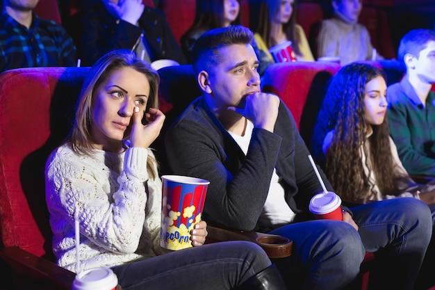 Amis pleurant en regardant un film triste au cinéma