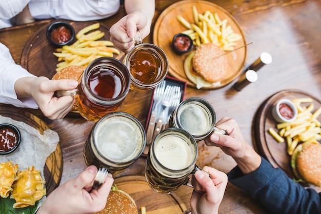 Amis portant un toast à la bière au restaurant