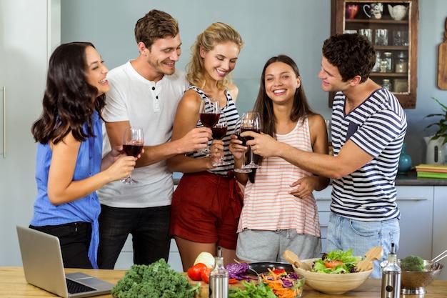Amis portant des verres à vin à la maison