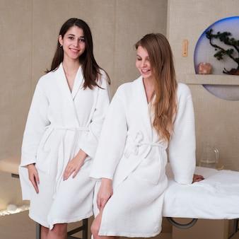 Amis posant dans des peignoirs de bain au spa