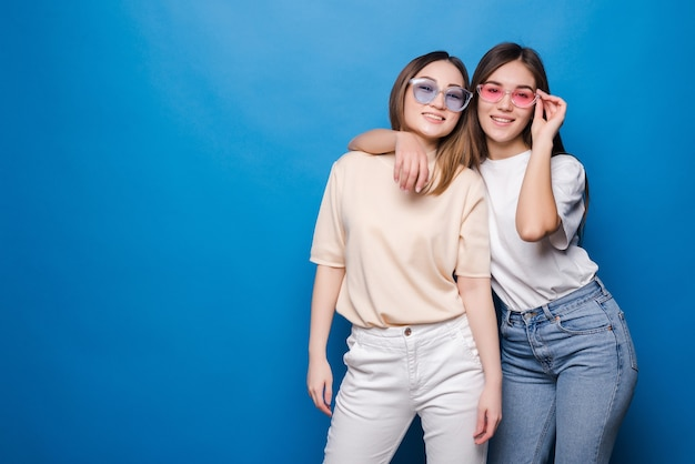 Amis pour toujours. deux jolies amies de jolie fille dans des lunettes de soleil posant avec sourire isolé sur mur bleu