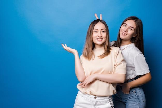 Amis pour toujours. deux jolies amies de jolie fille dans des lunettes de soleil posant avec le sourire sur le mur bleu