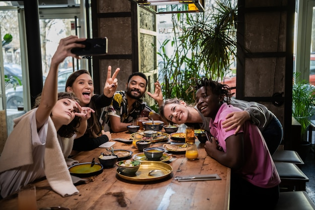 Amis prenant des photos d'eux-mêmes dans un café lors d'un dîner