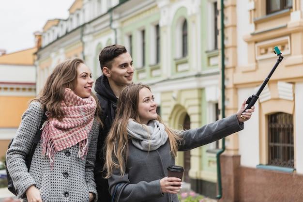Amis prenant selfie avec le bâton dans la rue