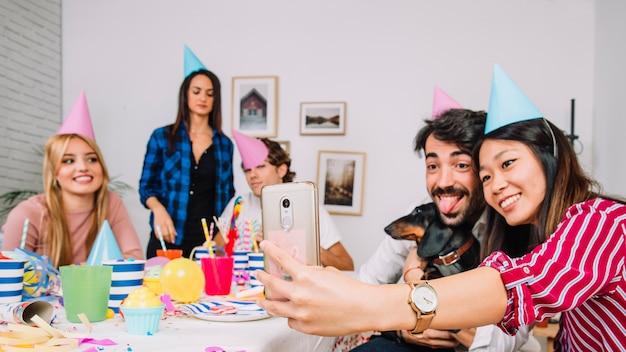 Amis prenant selfie à la fête d'anniversaire