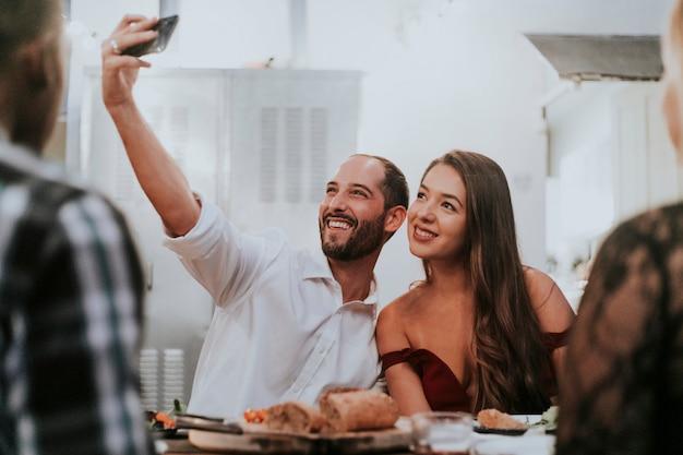 Amis prenant un selfie lors d'un dîner