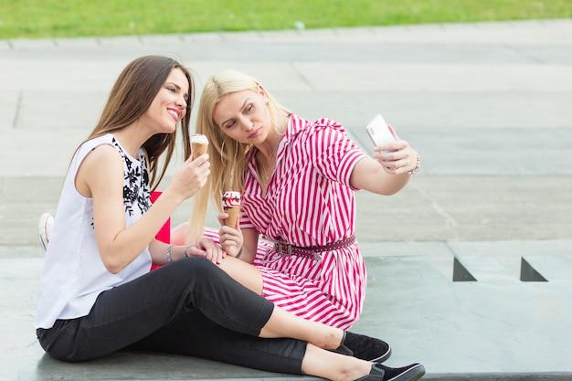 Amis prenant selfie en mangeant un cône de glace