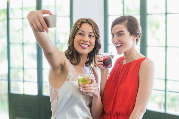 Amis prenant un selfie tout en tenant des verres à cocktail