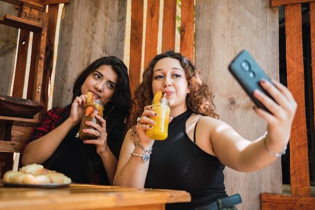 Amis prenant des selfies en regardant la caméra et en dégustant une boisson fraîche.