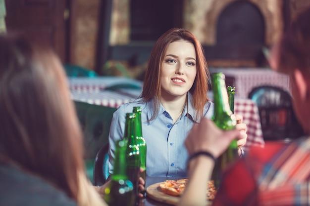 Amis prenant un verre dans un bar, ils sont assis à une table en bois avec des bières et des pizzas. concentrez-vous sur une magnifique fille qui touche sa bouteille.