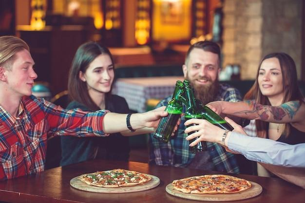 Amis prenant un verre dans un bar, ils sont assis à une table en bois avec des bières et des pizzas.