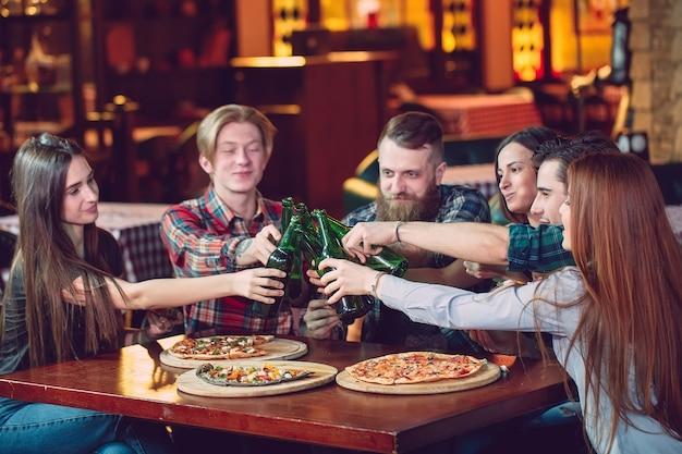 Amis, prendre un verre dans un bar, assis à une table en bois avec des bières et des pizzas.
