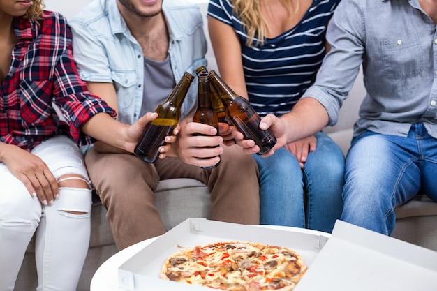 Amis profitant de bière et de pizza à la maison