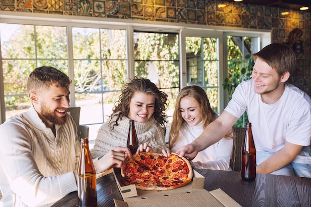 Amis quatre deux hommes et deux femmes heureux ensemble à table en train de manger de la pizza