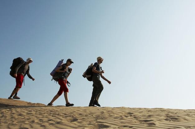 Amis qui montent le long de la colline en montagne