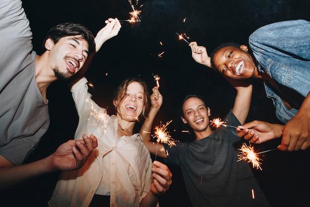 Amis de race mixte jouant avec célébration de feux de bengale et concept de fête