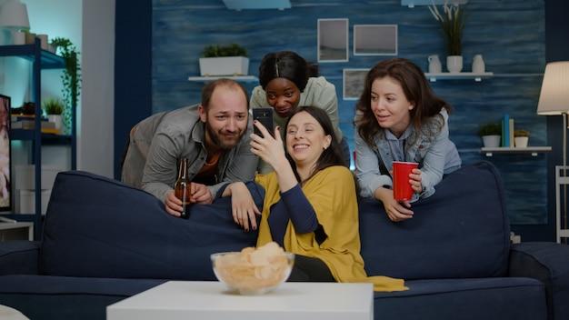 Des amis de race mixte se détendent dans le salon pendant une soirée en regardant un film en ligne sur un téléphone d ...